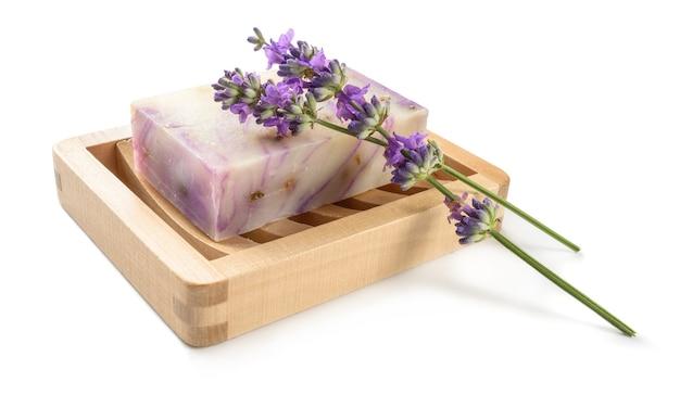 Sabonete caseiro de lavanda natural na saboneteira de madeira isolado no branco.