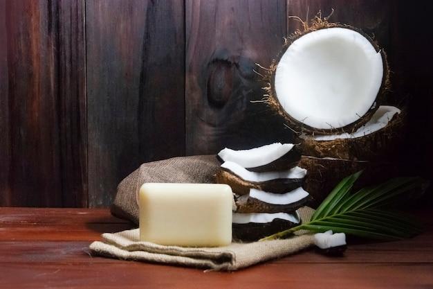 Sabonete de coco com metade de coco e pedaços de coco e folha na mesa de madeira