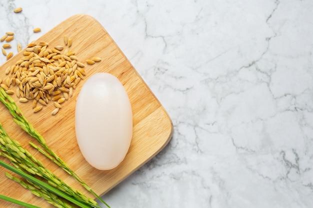 Sabonete de leite de arroz colocado em uma tentativa de madeira com plantas e sementes de arroz