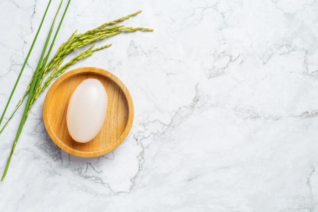 Sabonete de leite de arroz colocado em uma tigela de madeira com plantas de arroz