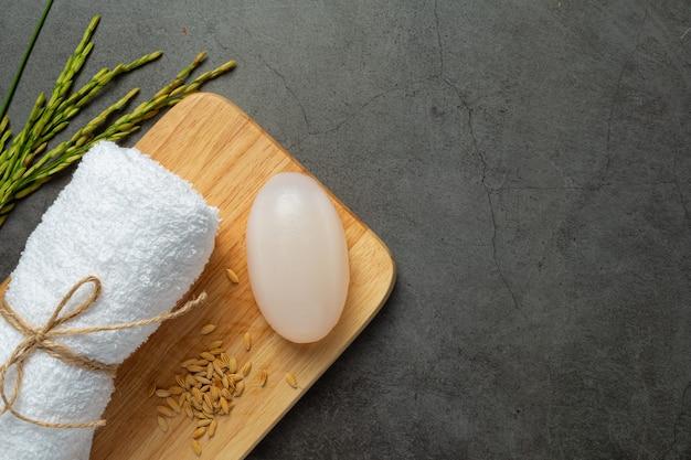 Sabonete de leite de arroz, toalha enrolada, plantas de arroz e sementes de arroz colocadas em uma mesa de madeira