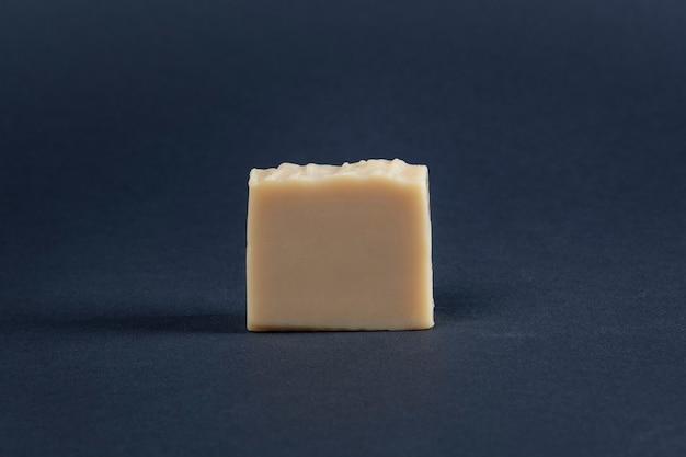 Sabonete em barra amarelo em uma superfície escura