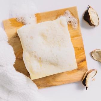 Sabonete em barra com espuma na placa de madeira perto de toalha e vagens de algodão
