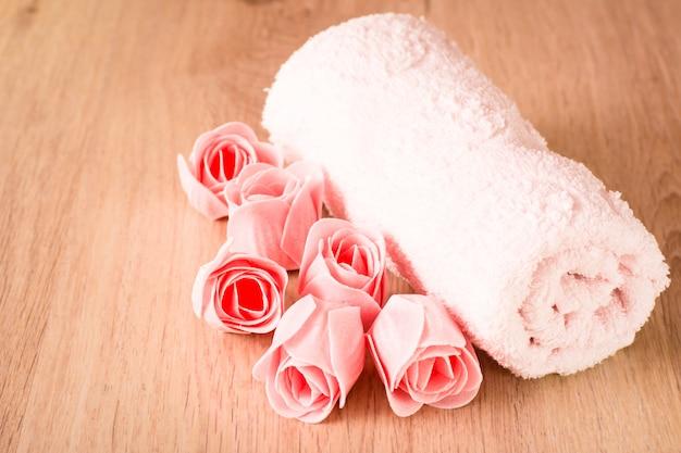 Sabonete em forma de rosas e uma toalha sobre um fundo de madeira