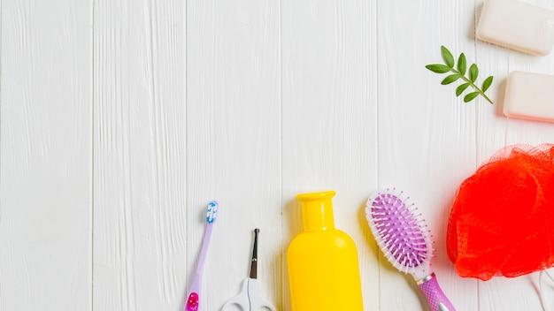 Sabonete; escova dental; tesoura; escova de cabelo e esponja no pano de fundo de madeira
