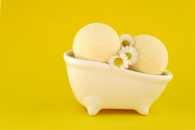Sabonete essencial de camomila e bombas de banho com extrato de camomila em um fundo amarelo brilhante