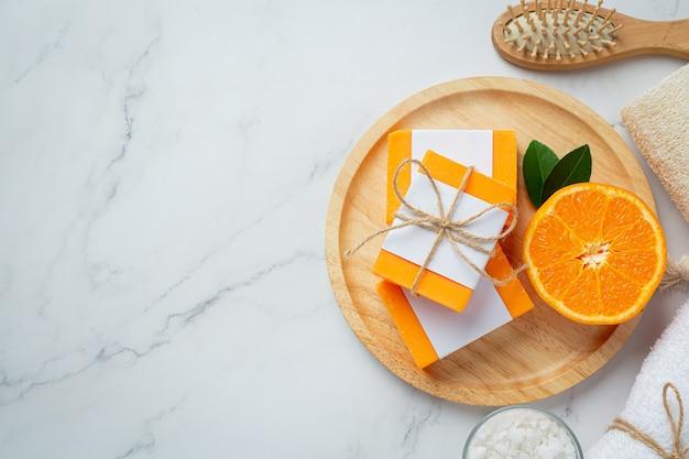 Sabonete laranja com laranja fresca sobre fundo de mármore