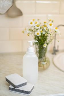 Sabonete líquido não tóxico ecológico com flores de camomila pratos limpos e brancos