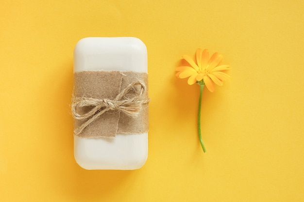 Sabonete natural artesanal decorado com papel artesanal e flor de calêndula laranja na superfície amarela