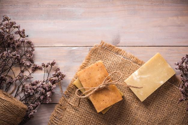 Sabonete natural com flores secas em fundo de madeira.
