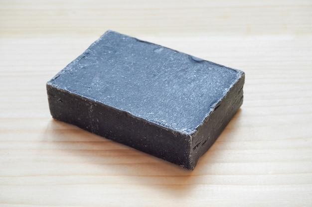 Sabonete orgânico preto. sabonete artesanal de carbono preto sobre fundo de madeira.