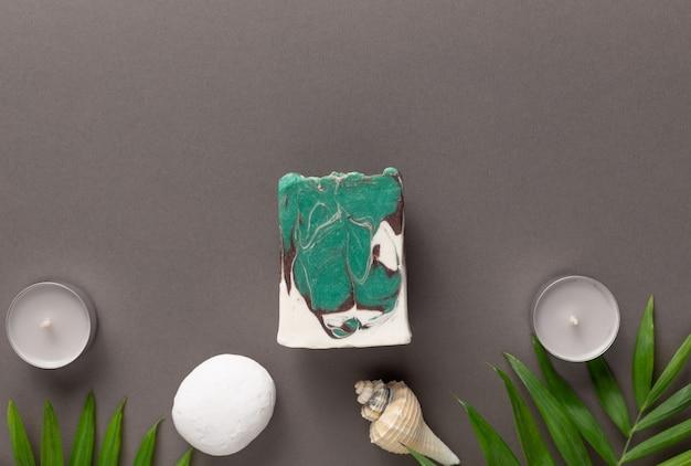 Sabonete perfumado feito à mão com óleos essenciais e ervas em fundo cinza. cosméticos orgânicos, conceito de spa. postura plana, copie o espaço