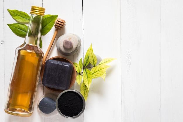 Sabonete spa preto feito de carvão ativado e mel no fundo branco de madeira