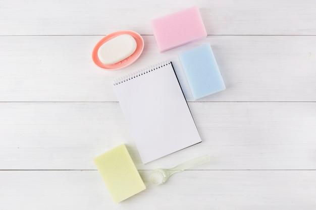 Sabonete; tipo diferente de esponja; caderno espiral e escova de plástico no fundo de madeira