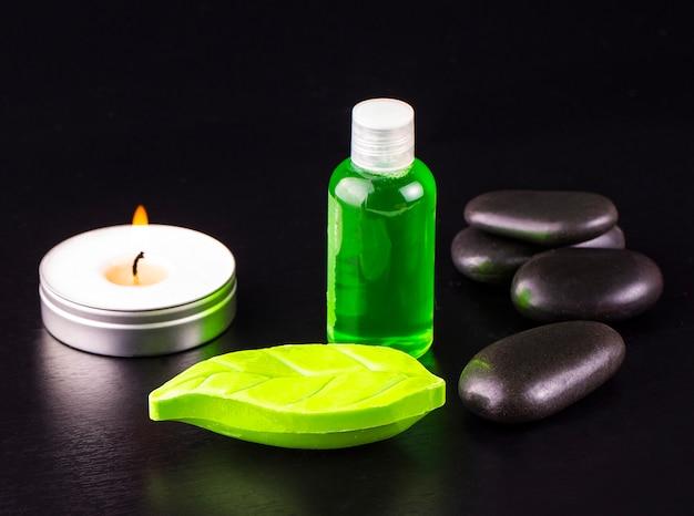 Sabonete, vela, garrafa de óleo e pedras spa na mesa preta.