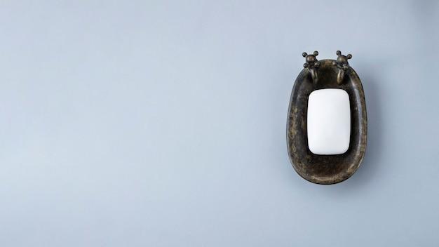 Saboneteira branca em saboneteira em forma de banho contra parede cinza. conceito de cuidados com o corpo e a beleza