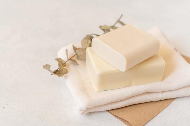 Saboneteira de madeira, papel ofício, tecido de algodão, sabonete, sobre fundo branco.