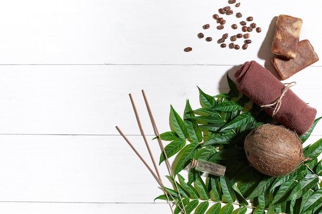 Sabonetes artesanais naturais com grãos de café, toalha marrom, coco e folhas verdes sobre fundo branco de madeira. vista do topo. copie o espaço. ainda vida. postura plana. conjunto spa