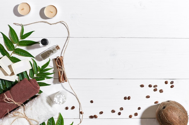Sabonetes naturais feitos à mão com grãos de café, esponja de sal marinho, toalha marrom e folhas verdes em madeira branca