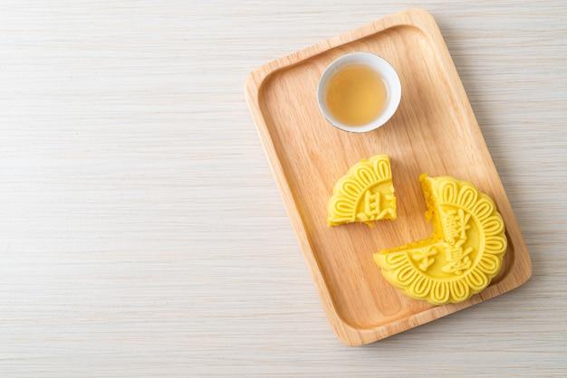 Sabor de pudim de bolo lunar chinês com chá no prato de madeira
