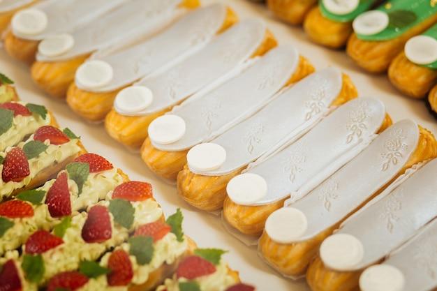 Sabor delicado. close up de éclairs de baunilha cobertos com chocolate branco macio e doce