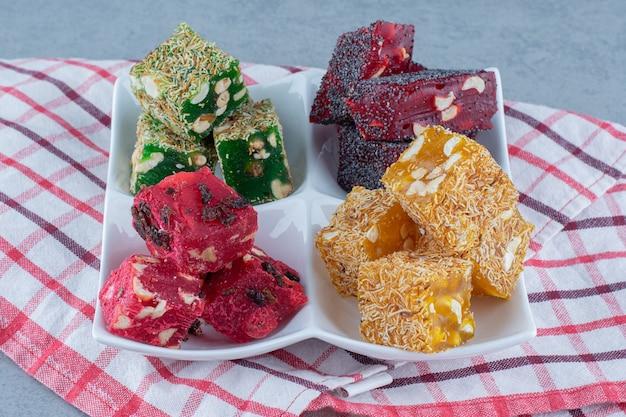 Sabores de delícias turcas coloridas em uma tigela, no pano de prato, na mesa de mármore.