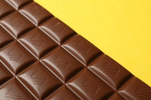 Saborosa barra de chocolate em fundo amarelo