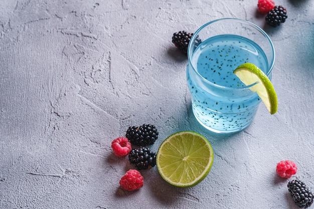 Saborosa bebida de cocktail de cor azul com sementes de manjericão chia, fatia de limão cítrico, bagas de framboesa e amora em vidro, bebida saudável de verão, mesa de concreto de pedra, espaço de cópia de vista de ângulo