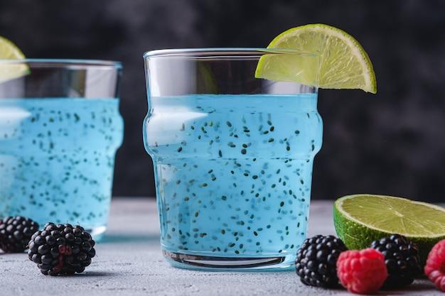 Saborosa bebida de cor azul com sementes de chia, fatia de limão cítrico, framboesa e amora em dois copos