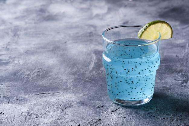Saborosa bebida de cor azul com sementes de manjericão chia e fatia de limão cítrico em vidro