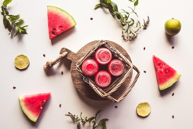 Saborosa bebida de melancia engarrafada de verão em uma cesta e fatias de frutas frescas em branco