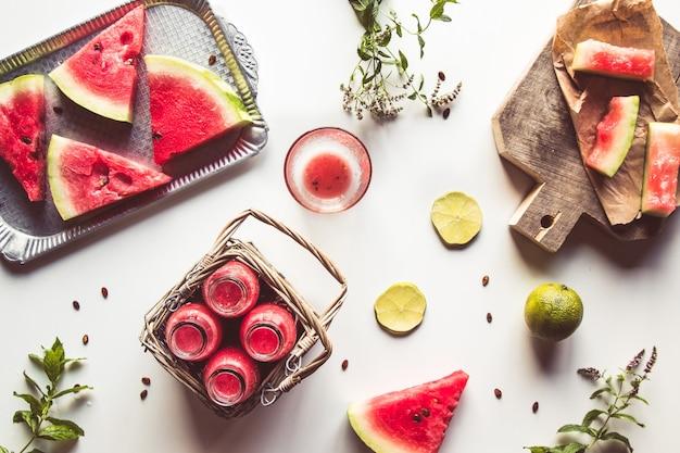Saborosa bebida de melancia engarrafada de verão em uma cesta e fatias de frutas frescas no fundo branco