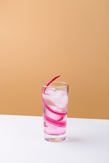 Saborosa bebida rosa com cubos de gelo na mesa branca