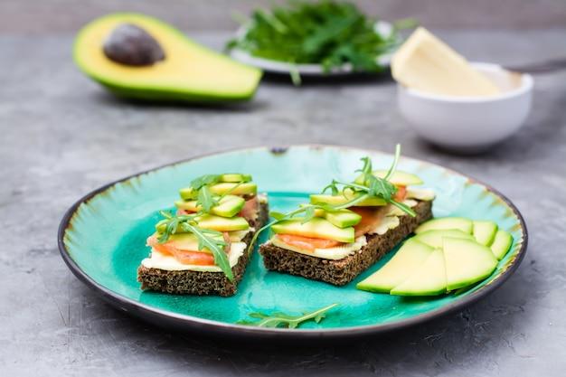 Saborosa bruschetta com salmão, manteiga, abacate e rúcula em um prato
