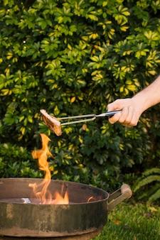 Saborosa carne grelhada em pinças de metal nas mãos