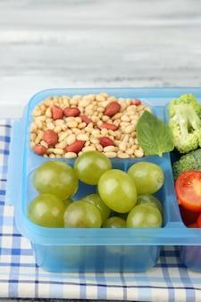Saborosa comida vegetariana em caixa de plástico na mesa de madeira