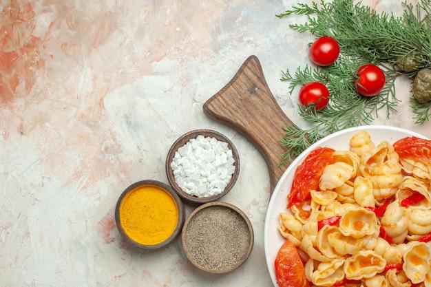 Saborosa conchiglie em um prato branco na tábua de madeira e uma faca de especiarias diferentes em fundo de cor mista