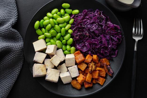 Saborosa e apetitosa tigela vegan com tofu no prato. vista do topo