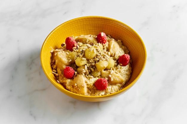 Saborosa e saudável aveia com sementes de mel, maçã, framboesa e girassol em uma tigela amarela brilhante sobre um fundo branco