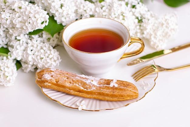 Saborosa éclair no prato com garfo e xícara de chá com buquê de flores