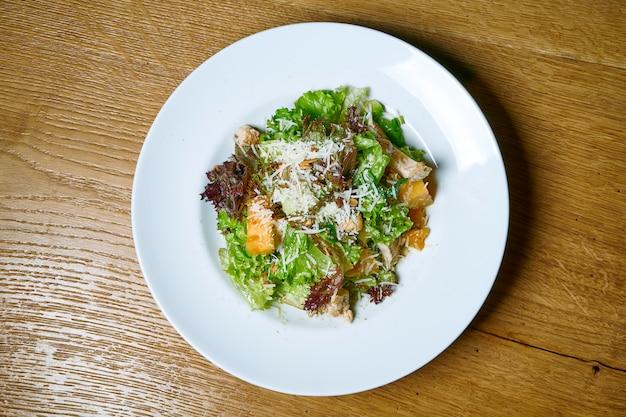 Saborosa, fresca salada com alface, parmesão e peru assado num prato branco sobre uma mesa de madeira. comida de vista superior. nutrição saudável