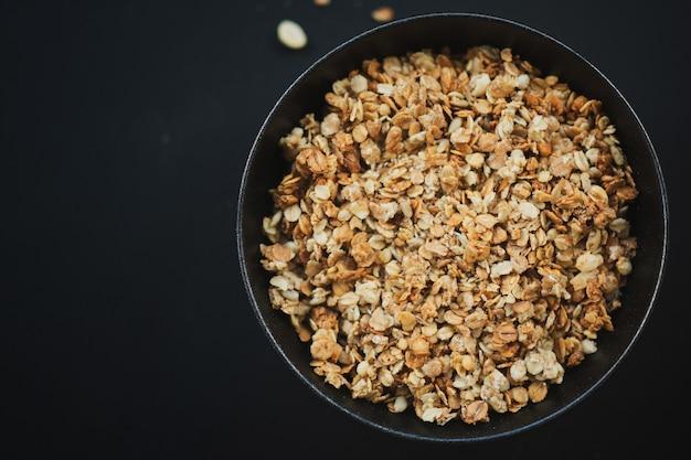 Saborosa granola de muesli caseira servida em uma tigela em fundo escuro. fechar-se