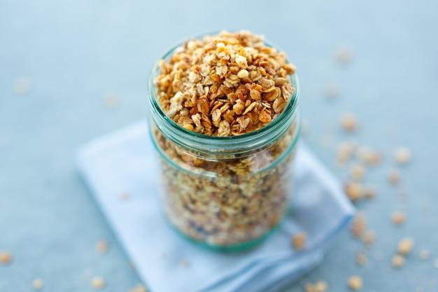 Saborosa granola de muesli frutada caseira em vidro no fundo brilhante. fechar-se