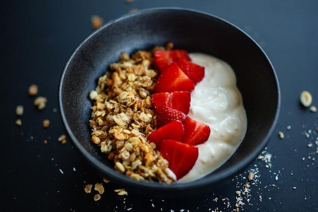 Saborosa granola de muesli frutada caseira servida em uma tigela com iogurte em fundo escuro. fechar-se