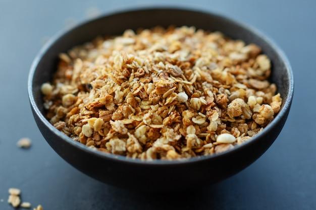 Saborosa granola de muesli frutada caseira servida em uma tigela em fundo escuro. fechar-se