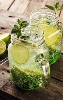 Saborosa limonada de bebida fresca fria com limão, hortelã, gelo e lima em vidro na mesa de madeira. fechar-se.