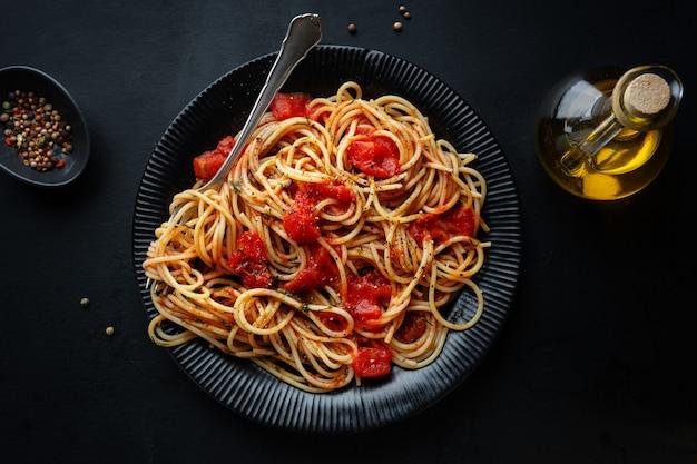 Saborosa massa italiana clássica com molho de tomate e queijo no prato em fundo escuro. vista do topo.