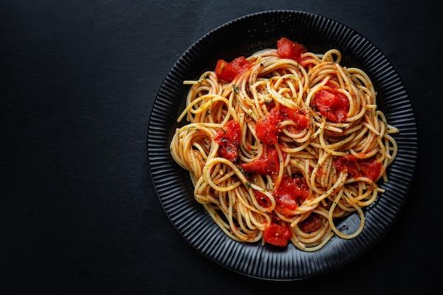Saborosa massa italiana clássica com molho de tomate e queijo no prato. vista do topo.