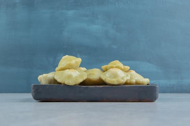 Saborosa mini abóbora na placa de madeira na superfície de mármore