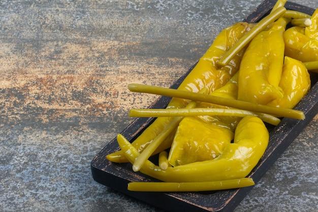 Saborosa pimenta fermentada e vara num prato de madeira.